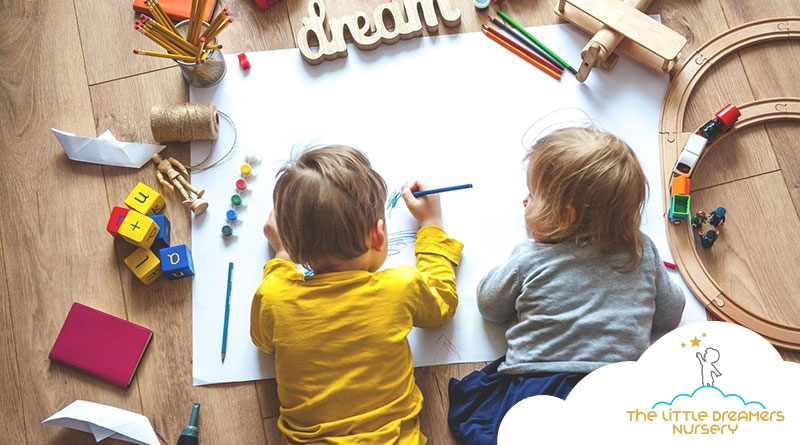 two cute babies are drawing in a nursery centre